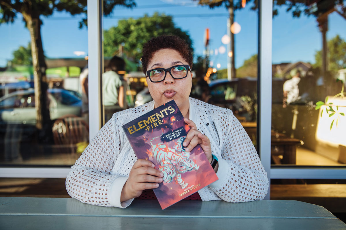 Taneka Stotts sits at a table holding a comic anthology.